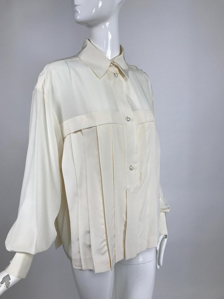 Chanel off white silk pleated long sleeve blouse, with amazing pearl logo buttons.Pull on blouse has a placket front with wing collar, vertical pleats beneath the yoke at the front and back. Long sleeves are full, with button cuffs. Marked size 40.