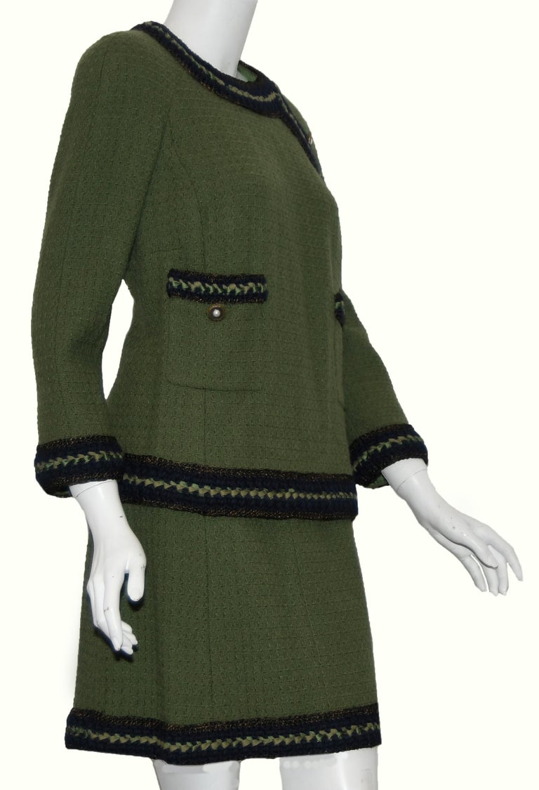 Chanel olive green skirt suit includes navy blue trim on sleeves, cuffs and hem of jacket and skirt.  The navy trim is accentuated with green ribbon and gold tone faux pearl buttons.  The skirt has a back zipper for closure and the top, 3 buttons