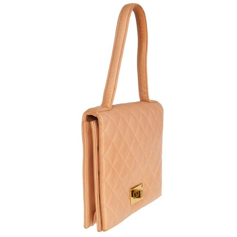 Chanel Vintage quilted flap handbag in pale salmon lambskin. Opens with a gold-tone turn look to a calfskin leather interior with one zipper pocket and one open pocket against the back. Has lipstick mirror under the flap. Has been worn and is in