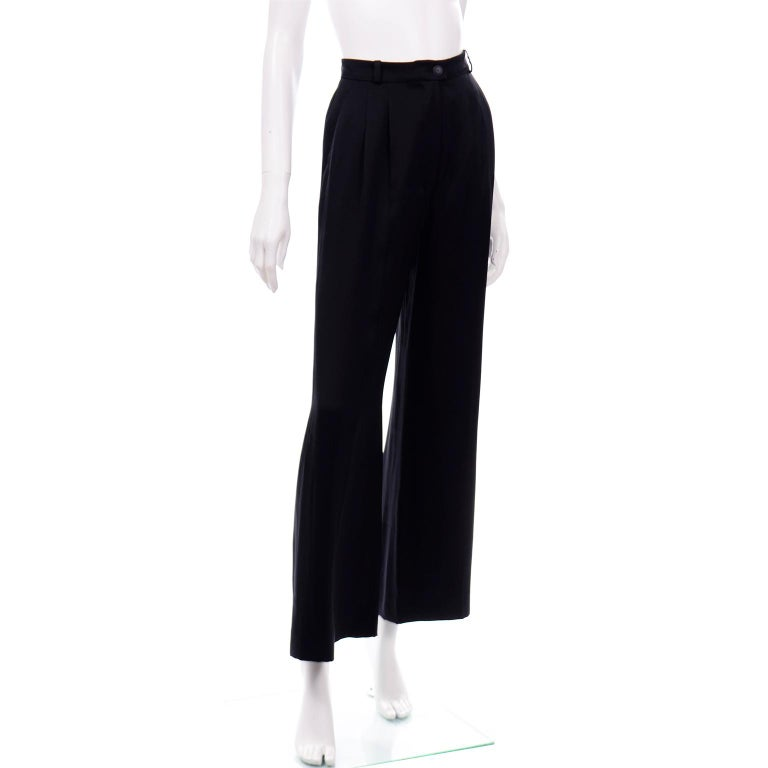 These are really elegant black silk Chanel pants from the Spring 2002 collection. The pants are high waisted and have two pleats on the front and a center fold down the leg. The waistband really slim and has small belt loops and a center CC monogram