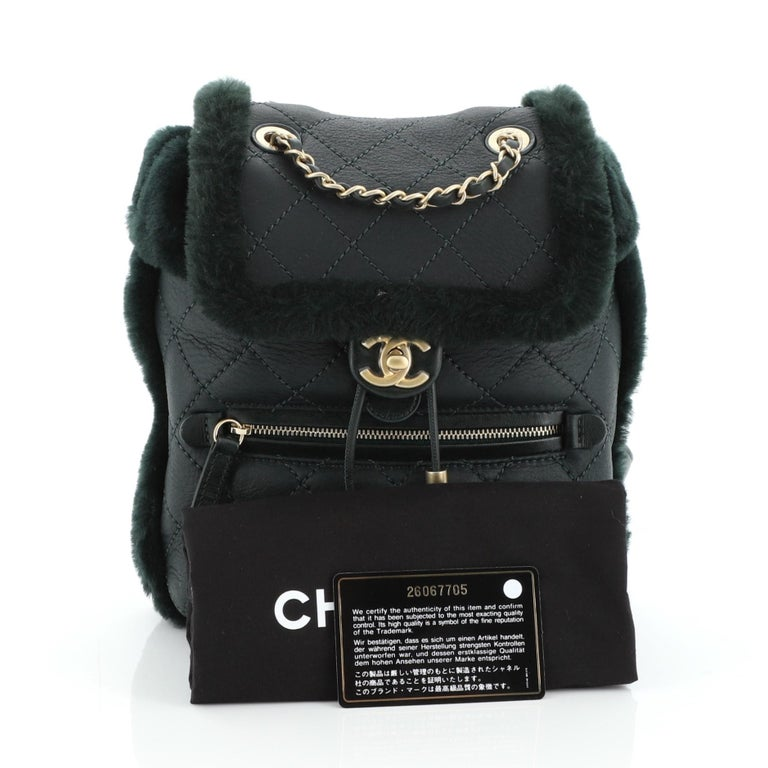 This Chanel Paris-Hamburg Flap Backpack Quilted Lambskin and Shearling, crafted in green quilted lambskin and shearling, features woven-in leather chain handle, leather straps, exterior zip pocket and gold-tone hardware. Its flap and drawstring