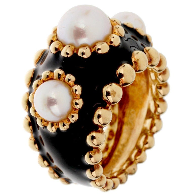 A lovely authentic Chanel ring circa 1990s showcasing 3 pearls each with a beaded row encased with black enamel in 18k yellow gold. The ring measures a size 5 3/4