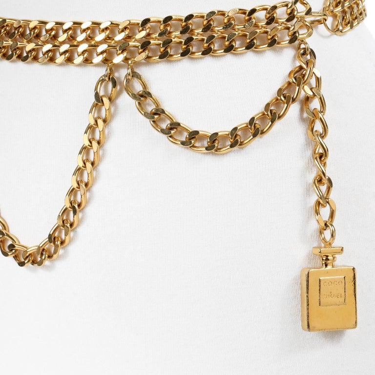 This authentic Chanel Perfume Bottle Triple Chain Belt is in beautiful condition.  Substantial double layer of gold tone linked chain with a third draped chain.  Gold COCO CHANEL perfume bottle dangles from the end.  Hook closure.  Measurements: