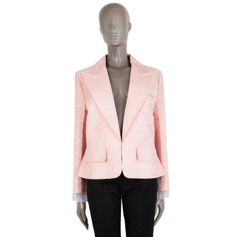 authentic Chanel 'Paris-Cuba' peak-collar blazer in baby pink silk duping (100%). With two flap pockets on the front, back slit, signature chain around the inside of the hemline, and detachable pleated cuffs in off-white polyester tulle (100%).