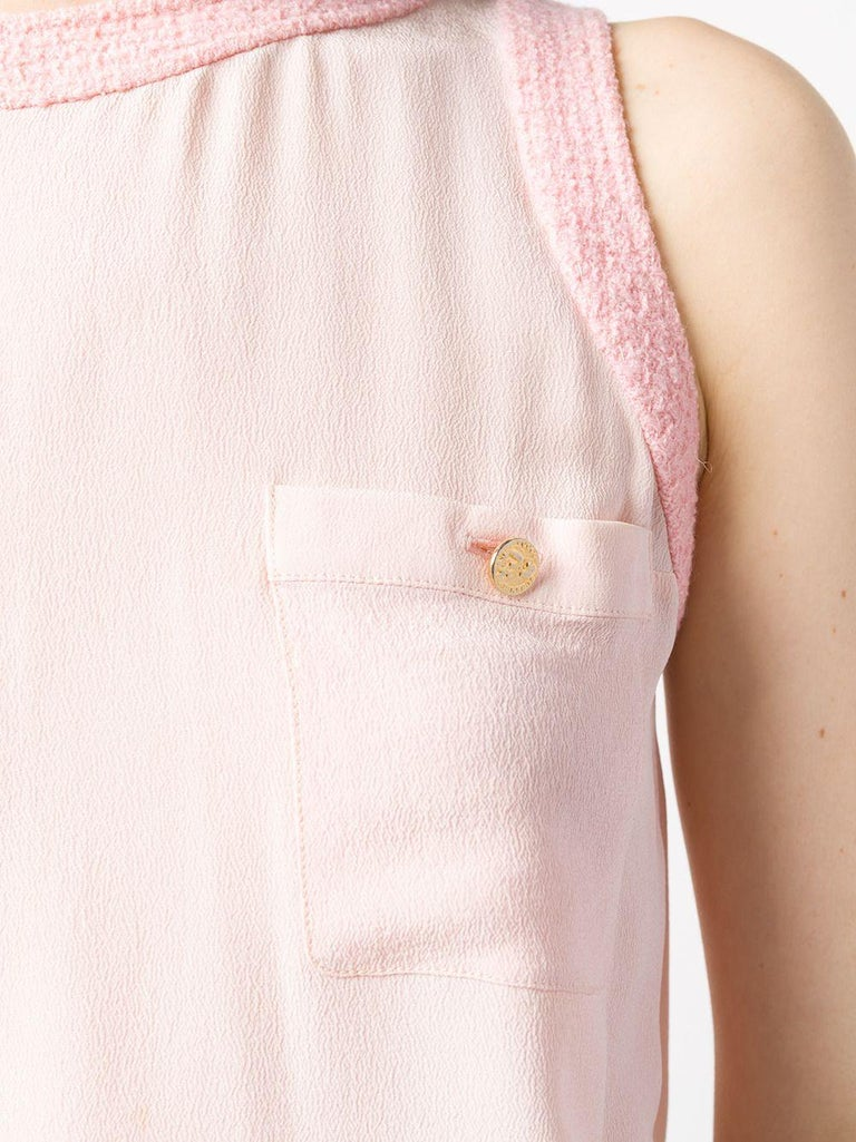 Expertly crafted in France from pure powder pink silk, this classic, pre-owned blouse perpetuates Chanel's finesse with a sleeveless design, a fluid style and bold, textured tweed framing the round-neck and underarms. The straight hem and two chest
