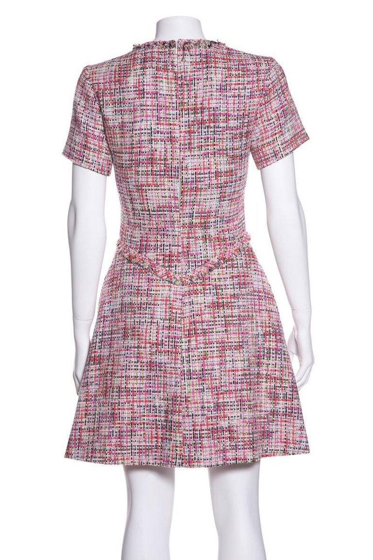 Chanel short sleeve, tweed v-neck dress with fringe detail, pockets and back zip closure. This item is previously worn with no major signs of wear. Made in France Shell: Cotton/Nylon/Rayon Lining: Silk   Size 34   Bust: 32