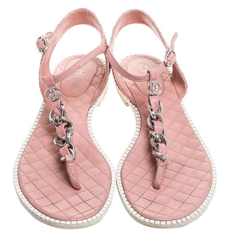 These stunning thong sandals by Chanel are a must-have. Crafted from leather, they come in love hues of pink and white. They feature the iconic quilted pattern on the ankle strap and footbed, the signature leather and chain detailing forms the main