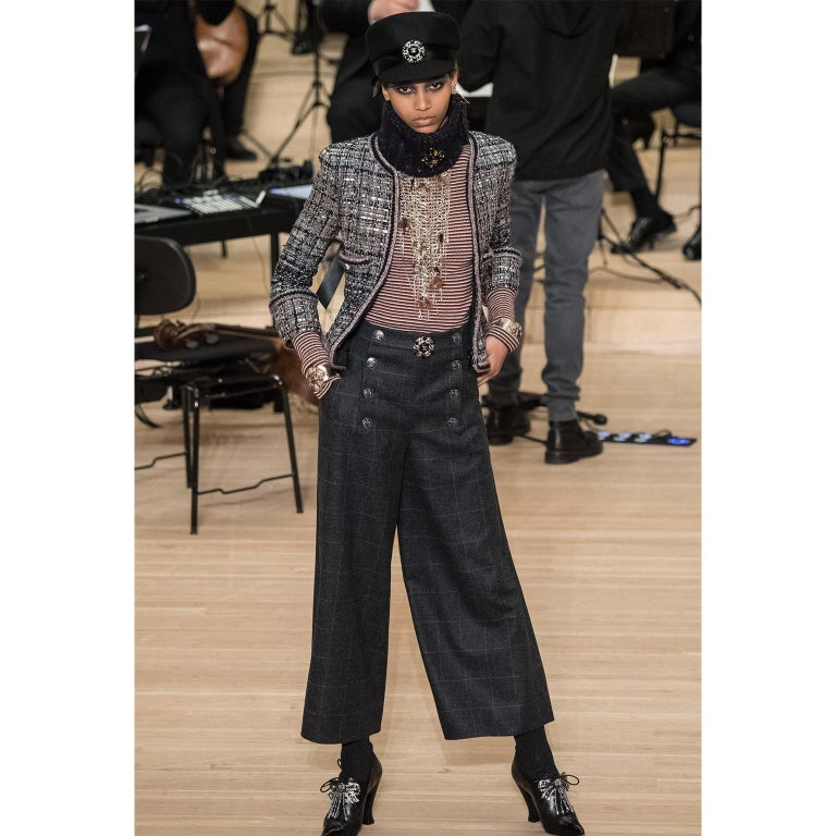 These are new with original tags Chanel Pre-Fall 2018 charcoal grey wool trousers with windowpane blue grid lines throughout. The front of the pants have a sailor style button panel that conceals the front zipper opening and a hook and eye closure.