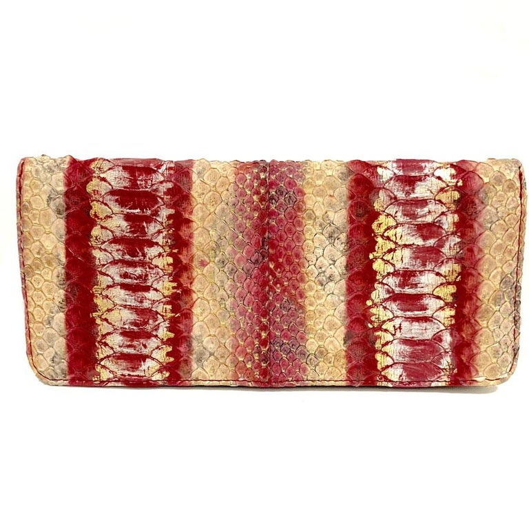 Gorgeous! Couture CHANEL pocket square entirely in python whose colors are a gradient from beige to red through pink. 5 decorated rectangular metal pieces are located in the center of the pocket in an aged gold metal. The pocket closes with a press