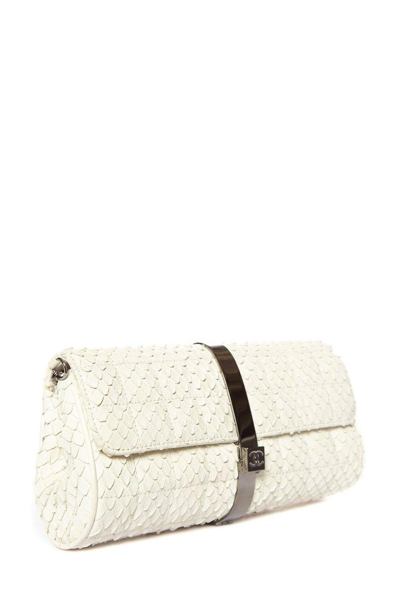 This Chanel clutch comes in an exotic cream python texture. The clutch is accented by a gunmetal gray chain and wrap around metal detail locking in the front with the classic Chanel logo.   This item is in excellent condition with minor scratching