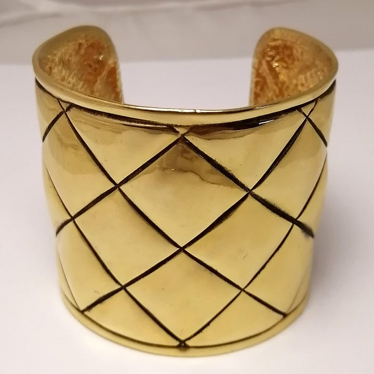 A 1980s French classic gilt metal bangle bracelet by Chanel. The rigid quilted design shows the CC logo on one of its sides and the brand's seal on the interior. It shows very mild marks of use.  Total dimensions: 6.3 x 6.8 x 5.8 cm. (2.5 x 2.63 x