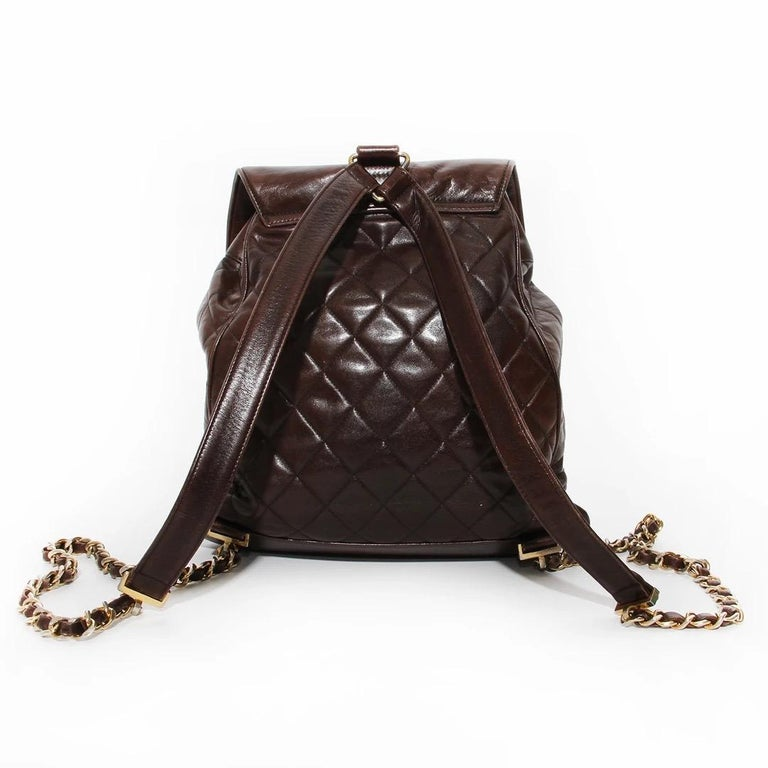 Chanel Backpack  Vintage  Circa 1990's Brown Lambskin  Quilted leather detail  Front flap with interlocked CC turn lock  Drawstring closure at top  Gold  Backpack style straps  Triangular gold hardware for straps Gold chain with leather detail on