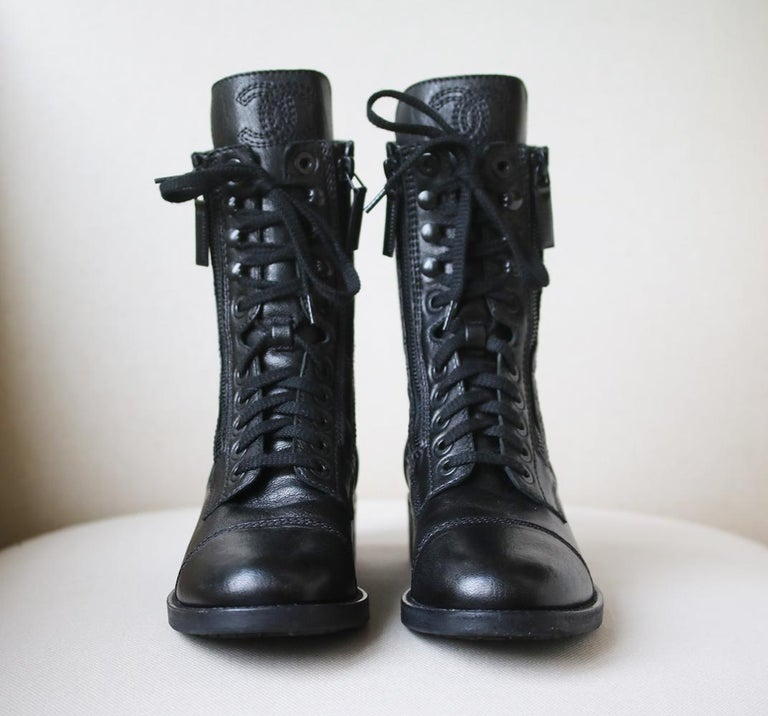 Chanel black leather calf-high boots with black leather toe cap. Heeled boot. Tonal black embroidered CC logo on the flap. Leather toe cap. Lace up. Colour: black.   Size: EU 38.5 (UK 5.5, US 8.5)  Condition: Slightest wear to the soles; see