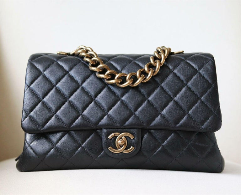 Chanel Quilted Leather Large Trapezio Flap Bag has been hand-finished by skilled artisans in the label's workshop. Boasting a soft quilted leather exterior, this design is accented with an oversized gold-toned chain hand and black lambskin-leather