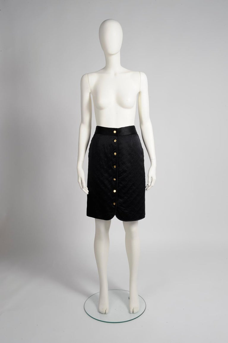 Cut in a classic pencil silhouette, this late 80's Chanel black satin silk skirt is expertly quilted to create texture and little dimension. Fully lined in black silk, it fastens down the front with seven gilt metal buttons with Chanel bag