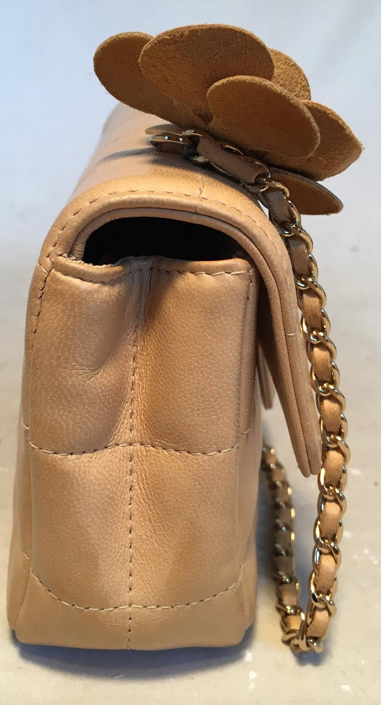 Chanel Quilted Tan Mini Camellia Classic Flap Shoulder Bag in good condition. Square quilted tan lambskin exterior trimmed with gold hardware and an adorable leather camellia flower along the top right side at one end of the woven chain and silk