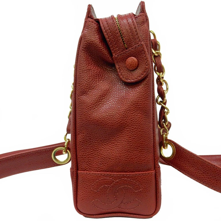 """- Vintage 90s Chanel red caviar leather tote shoulder bag.   - Featuring stitching """"CC"""" on the bottom on both sides.   - Red caviar gold-toned """"Chanel"""" tag zip closure.   - Interior pocket zip closure.   - Height: 9 inches. Length: 10 inches. Width:"""