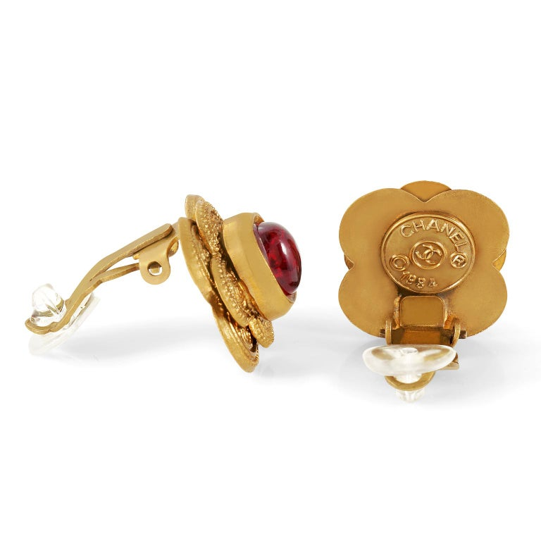 These authentic Chanel Red Gripoix Earrings are in excellent vintage condition from the 1984 collection.  Red Gripoix glass stones are centered on a double layer of gold flower cutouts.  Ornately detailed.  Clip on closure.  Made in France.  Pouch