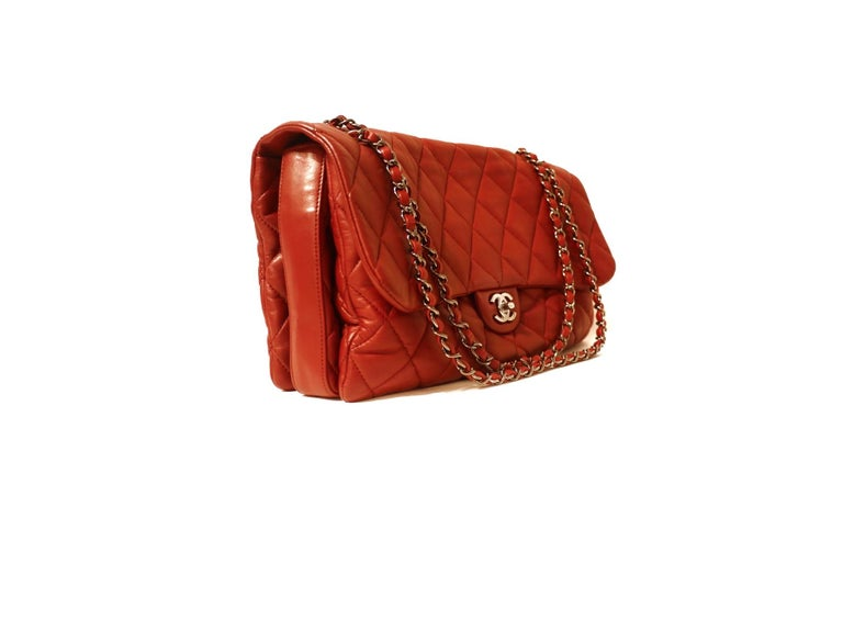 This authentic Chanel Red Lambskin Triple Accordion Flap Bag is in pristine condition.  A more yielding version of the classic flap, this is a roomy more relaxed daily shoulder bag.  Soft red lambskin is quilted in signature Chanel diamond pattern.