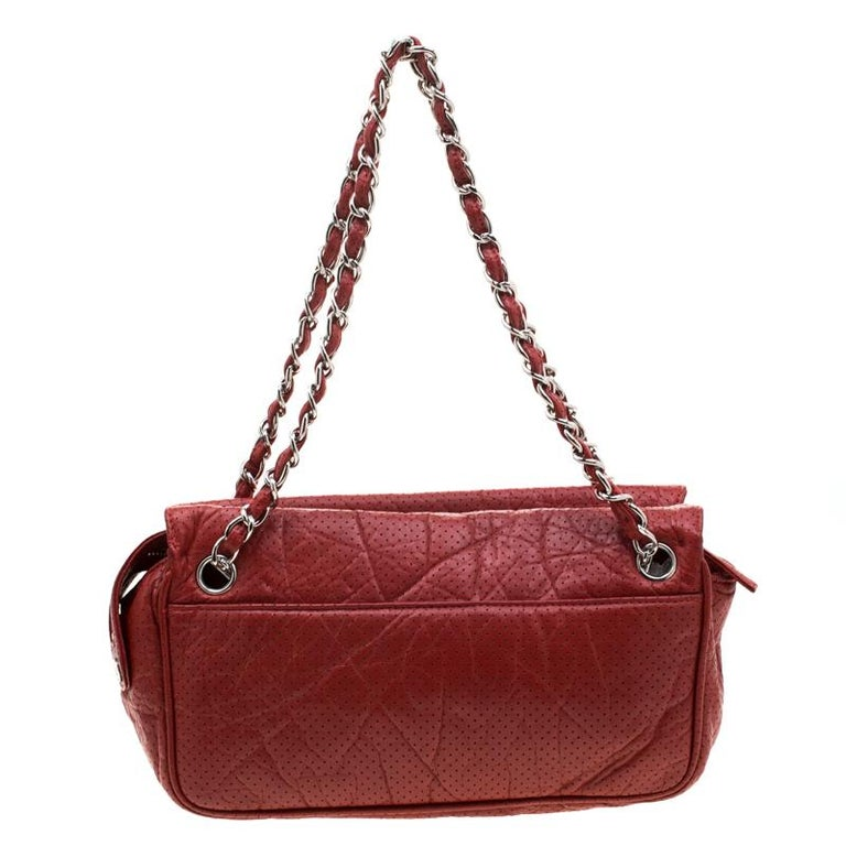 Now you can carry your camera around in this fancy Chanel Camera Bag. Made in France, this camera bag has been crafted out of perforated leather, lined with satin on the insides and sized to fit in your essentials. It has silver-tone hardware,