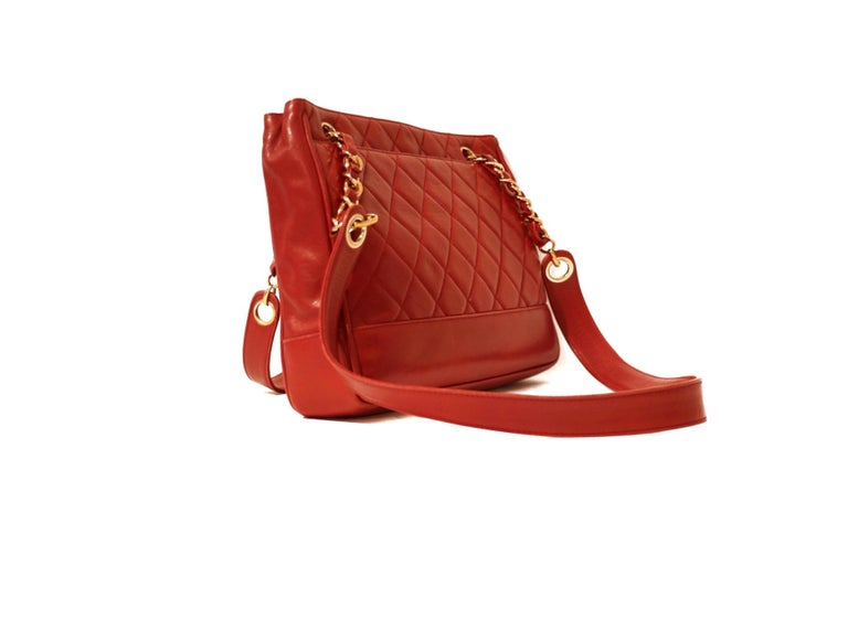 This authentic Chanel Red Quilted Leather Shoulder Bag is in excellent vintage condition.  Lipstick red leather is quilted in signature Chanel diamond pattern with smooth bottom and side panels.  Roomy front slip pocket and gold hardware accents.