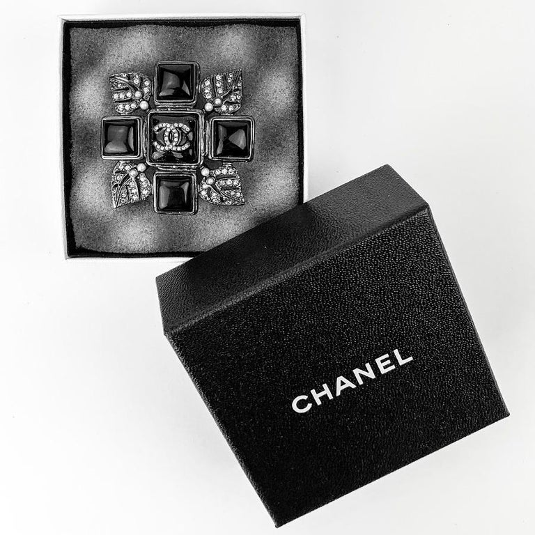 The brooch is signed by Maison CHANEL. It consists on a black resin cross around which come ruthenium metal sheets, set with rhinestones and pearls. We find the CC of the brand all in rhinestones in the center of the brooch. The brooch is in very