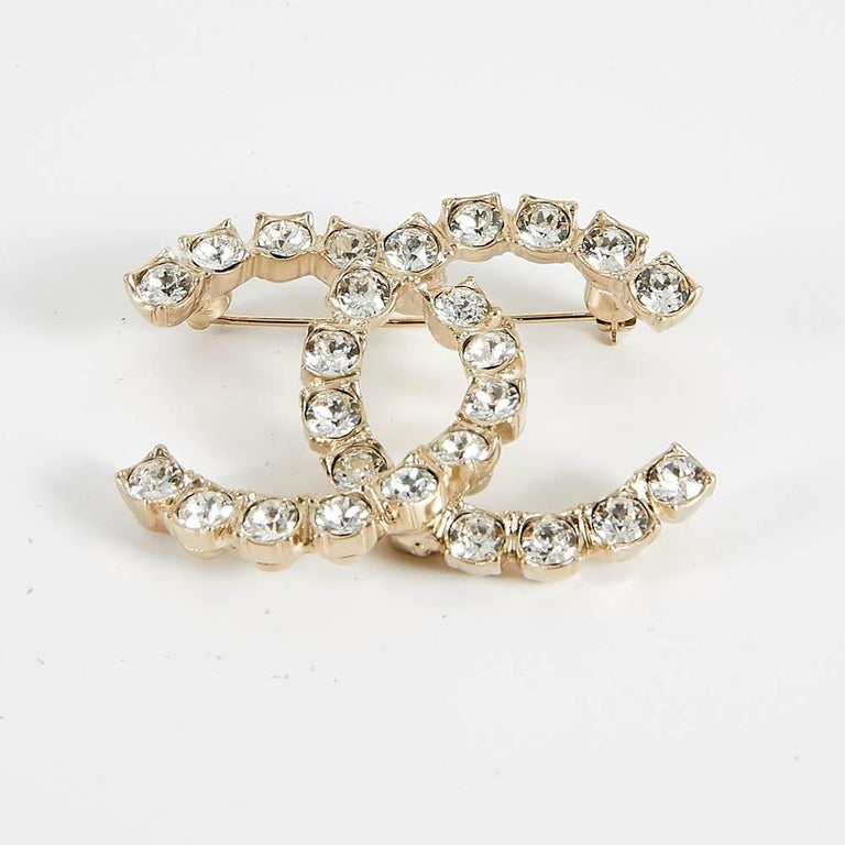 In mint condition, from 2020 summer collection, iconic Chanel interlocking CC logo brooch. With white rhinestone on gold toned metal. Measures : 5 x 3.7 cm.  It will be delivered in a non original dustbag.