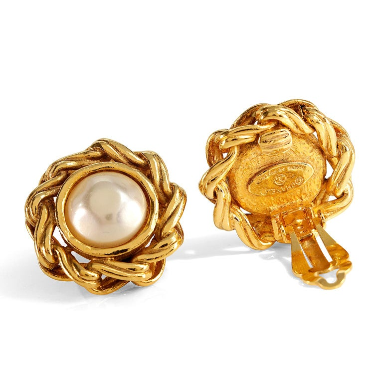 These authentic Chanel Gold Pearl Clip On Earrings are in excellent vintage condition.  From the 1980's, they feature a round faux pearl surrounded by a gold linked border. Clip on closure.  Made in France.