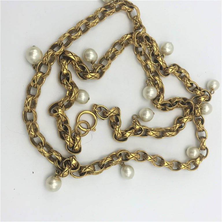 Timeless, typical CHANEL Sautoire, designed by Victoire de Castellane, signed 2CC3 = 1985 her 1st collection for CHANEL. Length of the sautoir 150 cm with the typical watch clasp. There are 12 false pearls hanging on the quilted gold-plated links  1