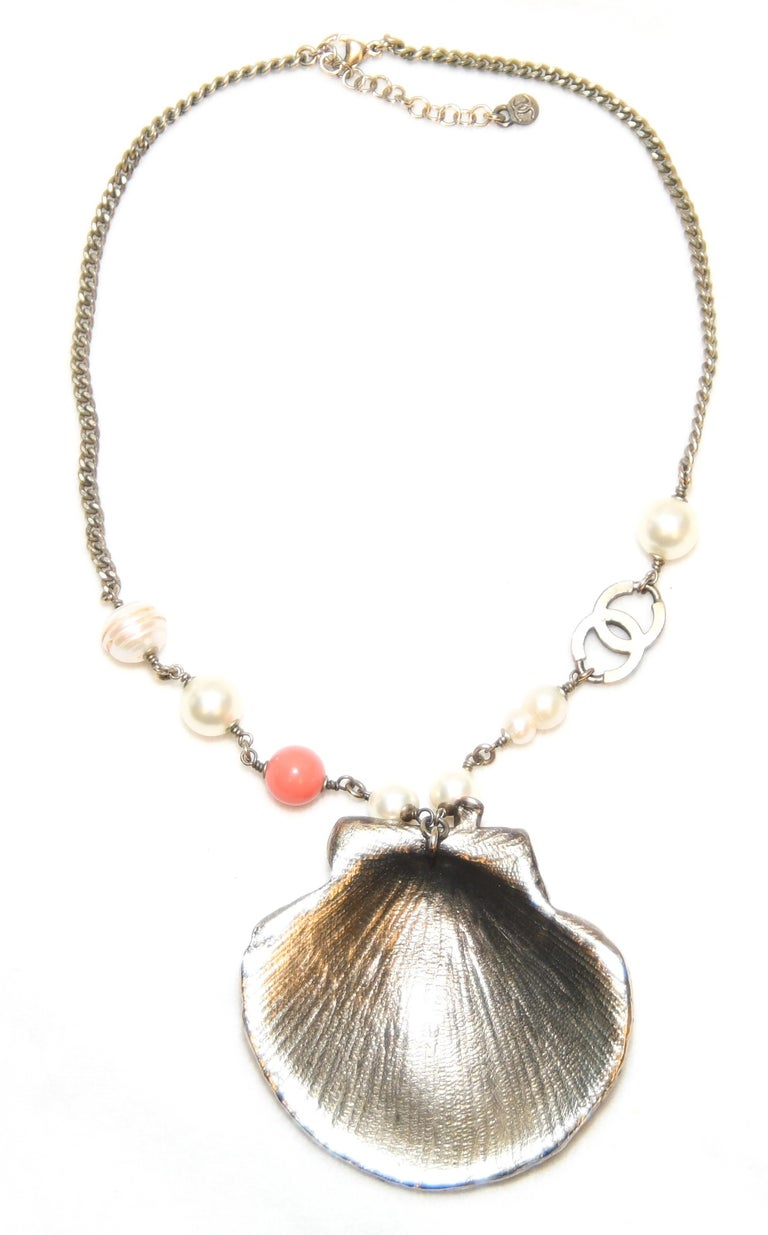 Distinctly Chanel!  Focal point features a Scallop shell adorned with bezel set crystals, crystal CC logos, a turbo star shell and a spiral cone shell each with crystals.  A coral branch enhanced by crystals is the focal point.  One coral bead