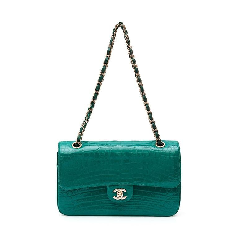 Crafted in France from exotic alligator leather in a highly sought after shade of emerald green, this iconic flap bag by Chanel is finished with the classic CC turn-lock in silver-tone hardware and features a fold-over top, a main internal