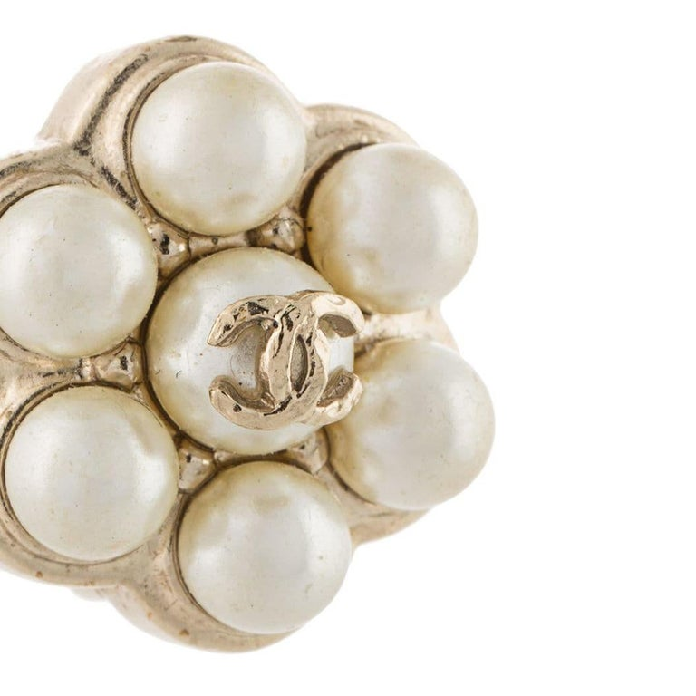 Add a little sophistication to your look with this pair of earrings by Chanel, crafted in France from gold-toned brass hardware and designed for the optimum elegance with a floral button-shaped design. These earrings feature a luminous faux-pearl