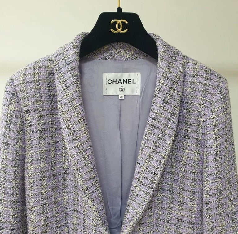 Chanel lavender long sleeve tweed jacket with dual front patch pockets and front hook closure. Shawl-collar.  This item is previously worn and in very good condition. Shell: Cotton/Polyester/Nylon/Rayon Lining: 100% Silk  It is from the Airport