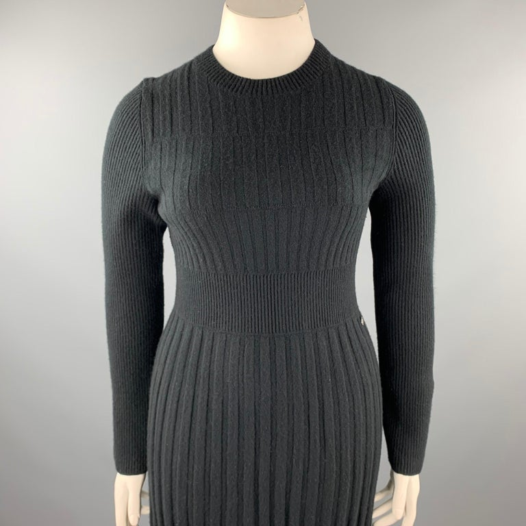 CHANEL sweater dress comes in a black knitted pleated wool featuring an a-line style, long sleeves, and a crew-neck. Made in Italy.  Very Good Pre-Owned Condition. Marked: FR 42 Original Retail Price: $5,640.00  Measurements:   Shoulder: 16.5 in.