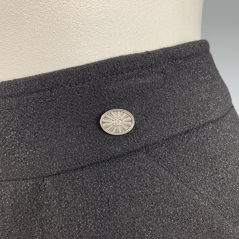 CHANEL pencil skirt comes in a black wool crepe with silver tone sparkle texture throughout slanted pockets, and a silver tone CC emblem at waist. Made in France.  Excellent Pre-Owned Condition. Retail: $1,600.00. Marked: FR 50  Measurements: Waist: