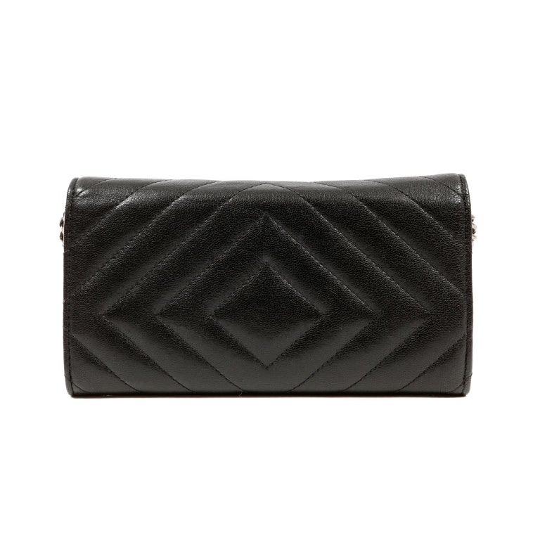 This authentic Chanel So Black Chevron Leather Wallet on a Chain is in excellent condition.  Highly sought after, the WOC easily organizes coin and currency with style. Black leather long wallet is quilted in chevron pattern.  All black mademoiselle