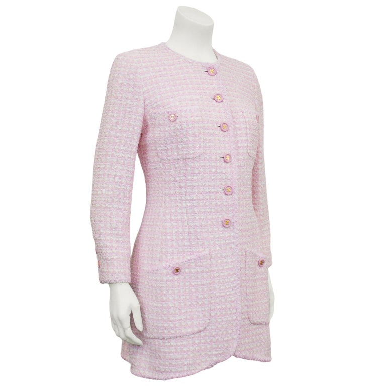 Pale pink and white bouclé jacket from the spring 1998 Chanel collection. Crew neckline, long sleeves, four large patch pockets and tulip hem. Large pink plastic round buttons with gold CC logos down front and at cuffs. White lining. Beautiful shape