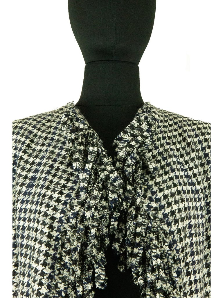 From the Chanel collection of spring 2007, comes this unique black and white dogtooth jacket. The bodice is loose fitting and cut on the bias, to give the two fronts of the jacket a draped feeling, as they fall into one another. There is also frayed