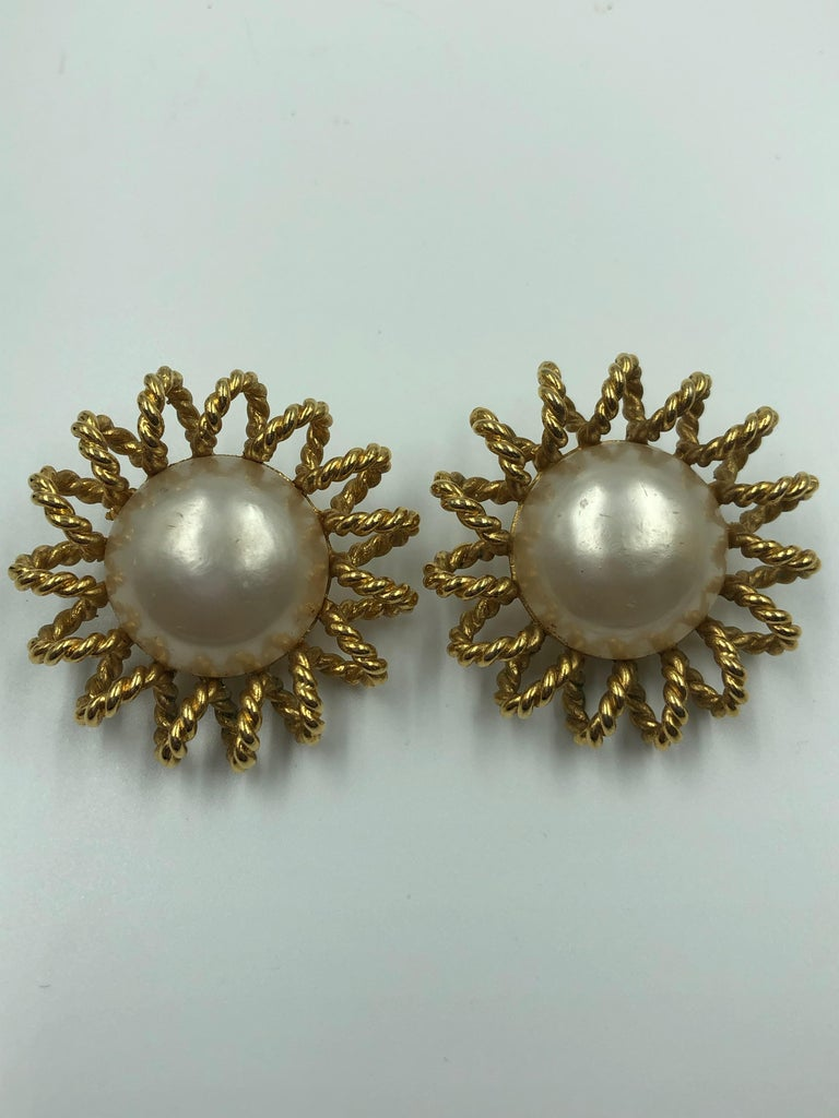 Channel gold-tone alloy starburst clip-on earring pair with Imitation pearl center.  Diameter:-1.5