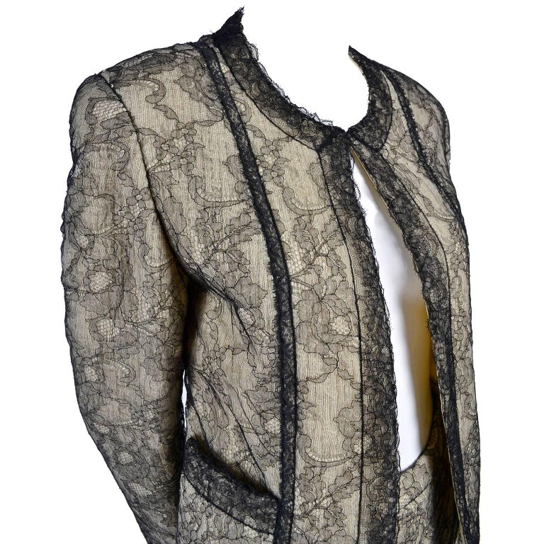 This is an absolutely gorgeous Chanel Boutique skirt suit that was originally purchased at Bergdorf Goodman. This suit is a cream wool boucle tweed with a black camellia flower chantilly lace overlay, and is fully lined in cream silk. The skirt zips