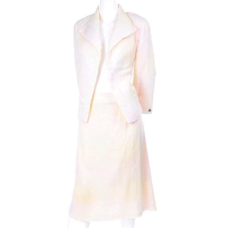 Vintage Chanel skirt suit in pastel shades of pale yellow and pink that fade in and out of each other similar to a faded ombre. This two piece skirt and jacket suit has intentional uniform