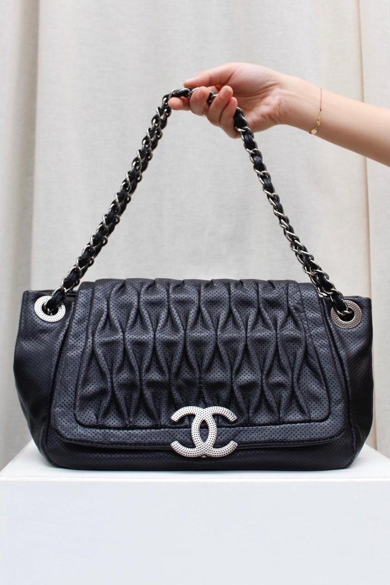 CHANEL (Made in Italy) Superb bag composed of perforated pleated black veal skin. It can be carried over the shoulder or cross-body by means of two sliding handles composed of silver plated chain entwined with black leather. The bag offers a