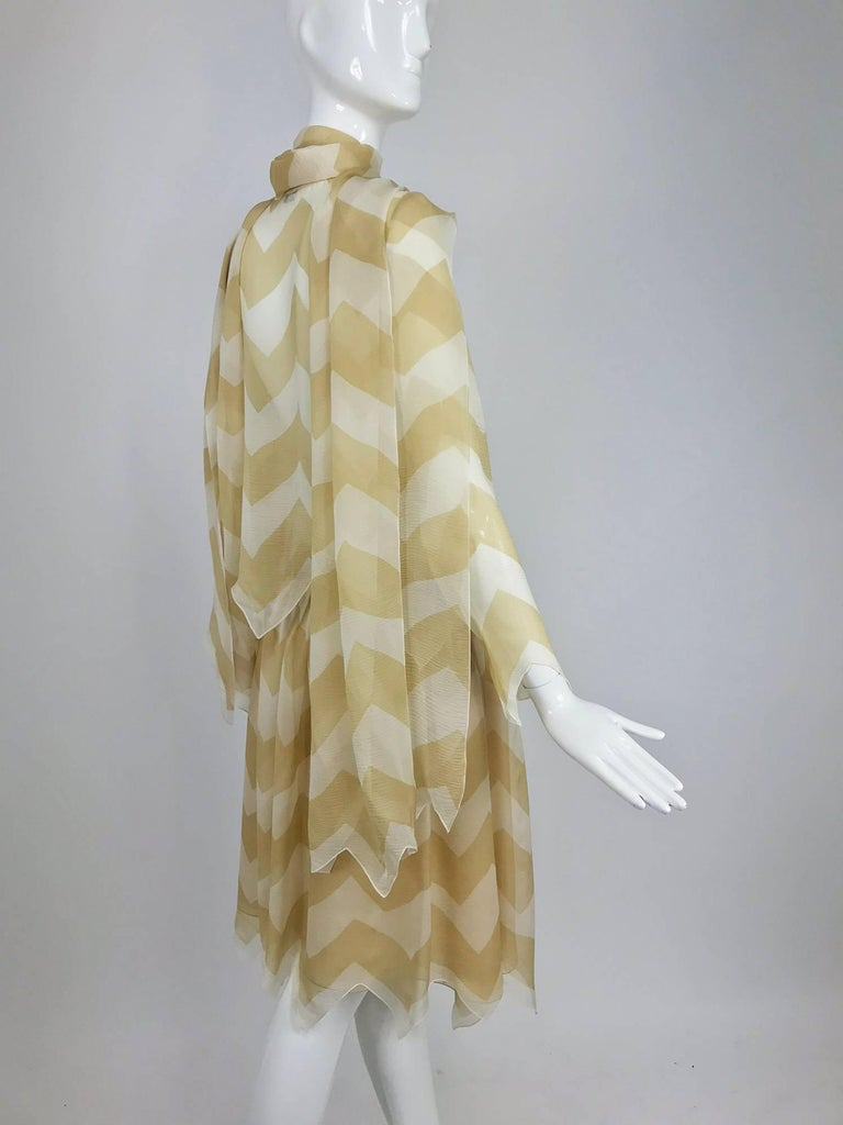 Chanel tan and cream silk chiffon zig zag pattern blouse and skirt 2000A...Sheer blouse is unlined, long sleeves with zig zag cuffs...Blouse buttons at the front with mother of pearl buttons, long and wide attached neck ties, will work as a shawl or
