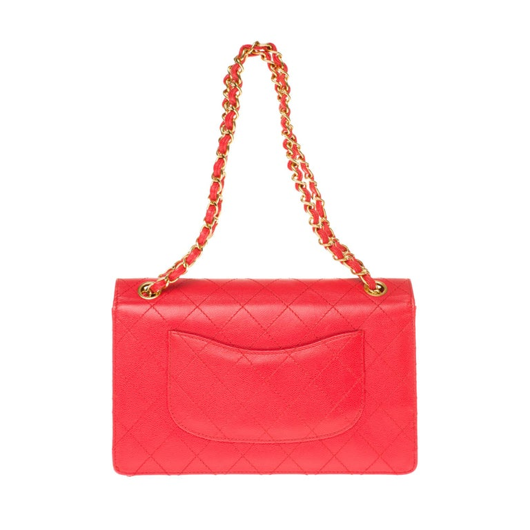 The iconic Chanel Timeless Handbag in red padded grained leather, gilded metal trim, a golden metal chain handle intertwined with red leather allowing a hand or shoulder support.  Gold-tone metal flap closure. A patch pocket on the back of the