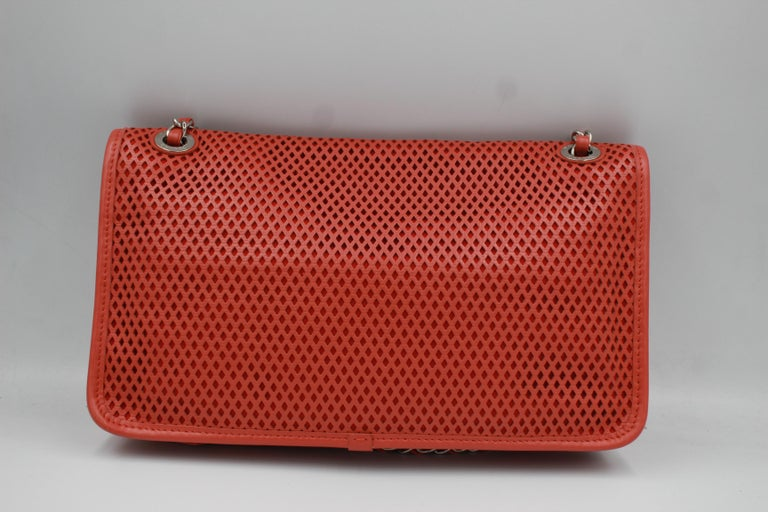 Chanel Timeless handbag in perforated leather. The color of the leather is between orange, red and corail. Rare piece from Chanel, collection 2013. Very good condition. Can be also wear crossbody. All set : dustbag and box. 18cm x 30cm x 6cm