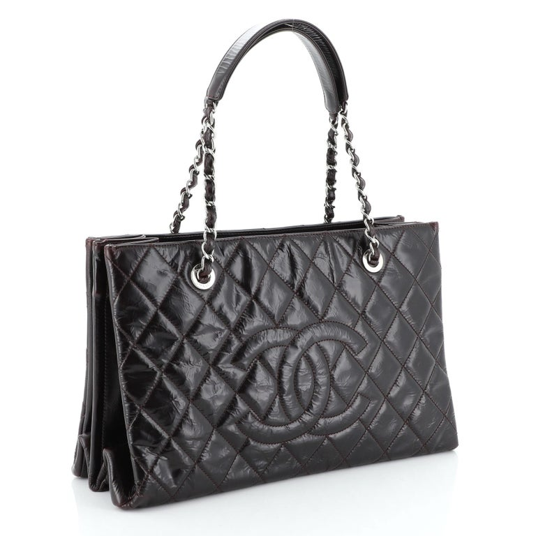 This Chanel Timeless Shopping Tote Quilted Glazed Calfskin Large, crafted from red quilted patent leather, features woven-in leather chain straps with leather pads, exterior back pocket, and silver-tone hardware. It opens to a gray satin and fabric