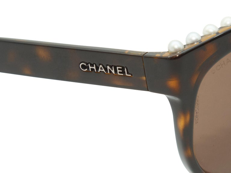 Product details: Tortoiseshell Chanel Pearl Trim Butterfly Shaped Sunglasses.  A line of pearls are perched on the top of the sunnies. The lenses are amber. Measurements: 5.5
