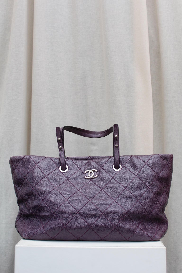 CHANEL (Made in Italy) Fabulous tote bag composed of over stitched eggplant color glazed leather. It can be carried by hand or over the shoulder, thanks to two adjustable leather handles.  It is decorated on one side with a silver plated CC logo.