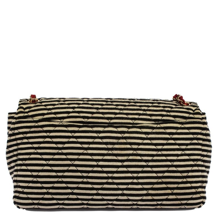 Add this beautiful Chanel Coco Sailer shoulder bag to your collection and carry the classic Chanel elegance with you at your day time and summer occasions. Crafted in black and white striped jersey fabric, this bag is accented with black leather