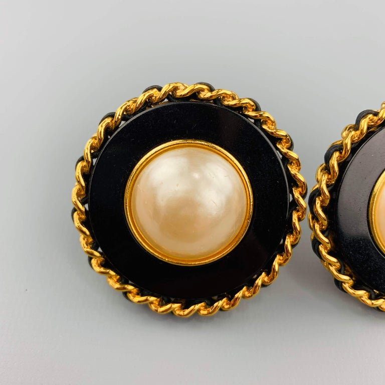Vintage CHANEL (Circa 1986-1992) Season 28 clip on earrings feature a black enamel round base with a faux pearl center and yellow gold tone metal leather woven chain boarder. Made in France.   Very Good Pre-Owned Condition. Marked: 28   5 cm.
